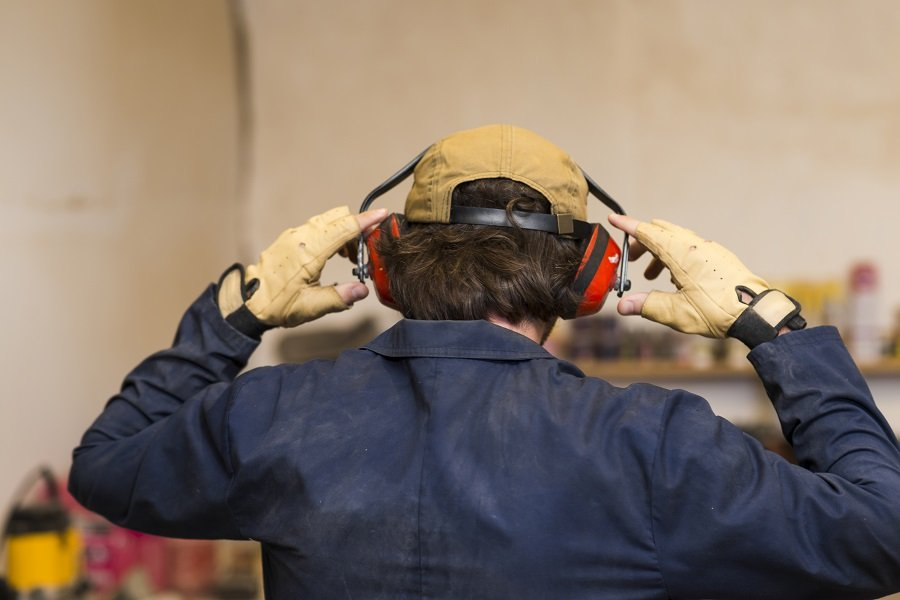 A man in his workshop wearing proper safety equipment.  This is one of the fundamental woodworking basics.