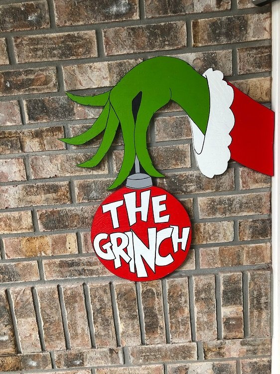 A Grinch hand holding an ornament to hang on your house or in your yard.