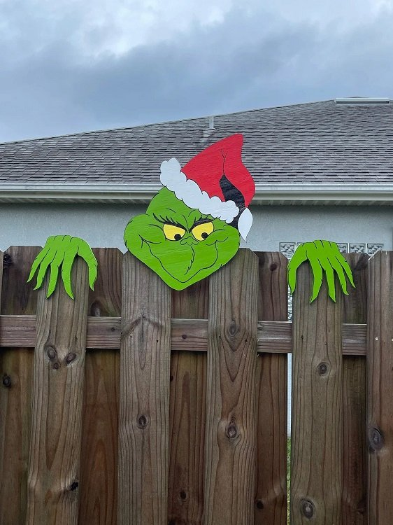 A wooden Grinch decoration where he's peeking over the fence.
