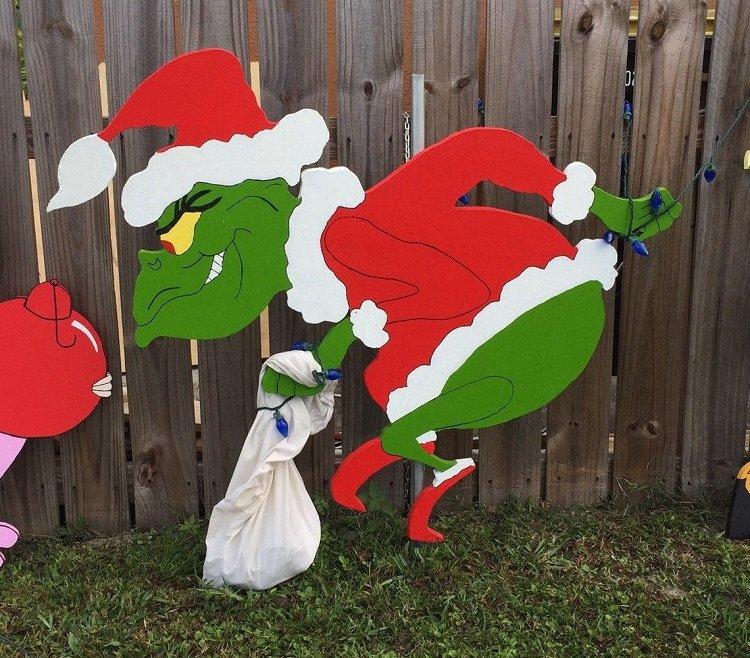 The grinch yard art, stealing Christmas lights.