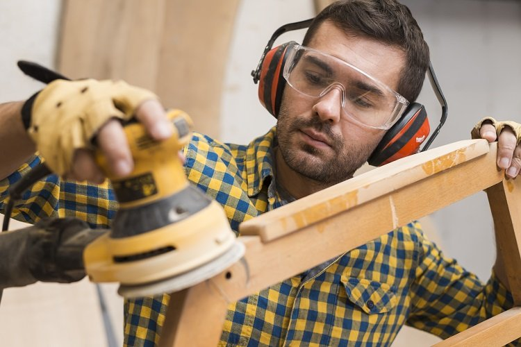 This is a picture of a man using a sander to make furniture.